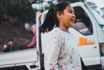 LAOS- FEBRUARY 18, 2018: Smiling young girl standing at truck and having fun. — Stock Photo