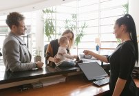 Reception worker giving key to young family at hotel lobby — Stock Photo
