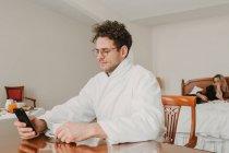 Hombre en albornoz de navegación smartphone en la habitación del hotel - foto de stock