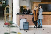 Vista posteriore della giovane famiglia alla reception nella hall dell'hotel — Foto stock