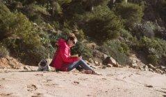 Vue latérale de la vue de la femme assise sur le bord de la mer et le livre de lecture et accompagnée d'un chien — Photo de stock