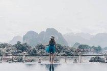 Vista posteriore della donna in abito in piedi sotto la pioggia e guardando le montagne tropicali . — Foto stock