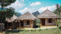 Bonitos pequenos bangalôs com telhados de palha no prado verde — Fotografia de Stock