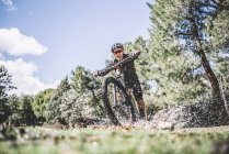Передний вид человека-велосипедиста брызгает водой с горного велосипеда на газоне — стоковое фото