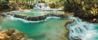 Panoramic view to small waterfalls flowing on sunny day — Stock Photo