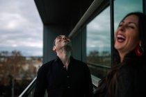 Portrait de couple gai rire sur balcon — Photo de stock