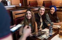 Обтинання офіціант приймати замовлення від друзів в ресторані — стокове фото