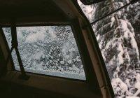 Finestra di automobile parcheggiata su strada innevata in inverno — Foto stock
