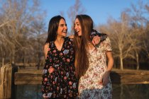 Cheerful young women embracing and walking along rural wooden fence. — Stock Photo