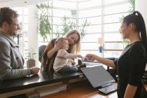 Staff giving key to young family at hotel lobby — Stock Photo