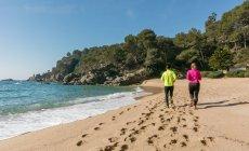 Vista traseira do casal correndo ao longo da praia deserta — Fotografia de Stock