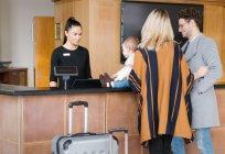 Реальный вид молодой семьи на стойке регистрации отеля — стоковое фото