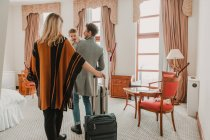 Vista posteriore della famiglia con le valigie a piedi nella camera d'albergo — Foto stock