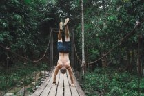 Rückansicht des nackter Oberkörper Mann auf Händen auf trashigen Holzbrücke — Stockfoto