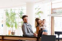 Família alegre com filho na recepção do hotel — Fotografia de Stock