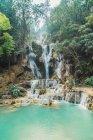 Vista a cascadas tropicales que fluye hacia abajo en el lago de turquesa - foto de stock