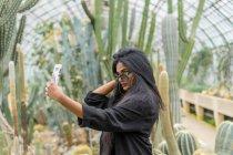 Молода жінка, беручи selfie в cactus в теплиці — стокове фото