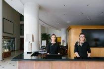 Zwei junge Frauen stehen an der Hotelrezeption — Stockfoto