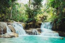 Piccole cascate pittoresche che scorrono verso il lago blu nella foresta verde . — Foto stock