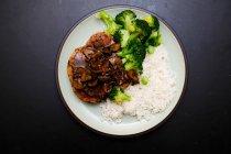 Direttamente sopra la vista di carne gustoso arrosto con salsa servita con riso e broccoli — Foto stock