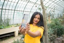 Jovem mulher étnica tomando selfie no cactus em estufa — Fotografia de Stock