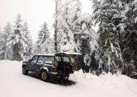 Vista laterale della macchina parcheggiata sulla strada innevata in inverno . — Foto stock