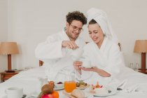 Cheerful couple having breakfast in hotel bed — Stock Photo