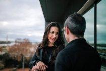 Mulher sorridente olhando para o namorado enquanto está de pé na varanda moderna . — Fotografia de Stock