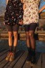 Low section of women standing on wood bridge in sunlight — Stock Photo