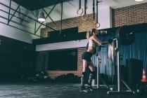 Подтянутая блондинка отдыхает после поднятия штанги в спортзале — стоковое фото