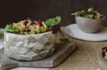 Bowls of salad of quinoa and red beans on table — Stock Photo