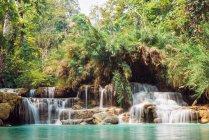 Идиллический вид на каскад водопадов, впадающих в озеро — стоковое фото