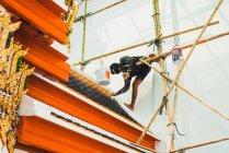 Чіанг Рай, Таїланд - 12 лютого 2018: декоратор людина висить на будівельному майданчику та живопису даху азіатських будівлі. — стокове фото