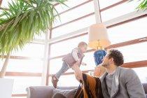 Fröhliche Familie mit Kind spielen auf couch — Stockfoto