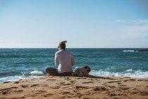 Mature woman sitting on seashore with pug dog aside — Stock Photo