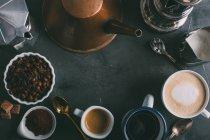 Diferentes tipos de café y cafeteras en fondo oscuro - foto de stock