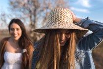 Alegres meninas jovens andando no campo em dia de sol — Fotografia de Stock