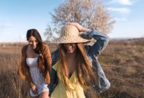 Cheerful young women holding hands and walking on field — Stock Photo