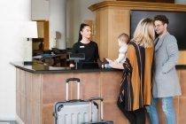 Famiglia con bambino e valigie parlare con il personale alla reception in hotel — Foto stock