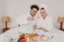 Cheerful couple eating breakfast in hotel bed — Stock Photo