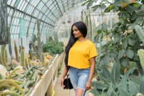 Young stylish Indian woman with handbag standing in hothouse. — Stock Photo