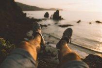 Beine des Menschen sitzen am Rande der Klippen am Meer — Stockfoto