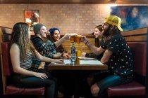 Amigos alegres batendo copos de cerveja à mesa no restaurante . — Fotografia de Stock