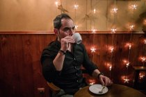 Замислений чоловік п'є каву в кафе — стокове фото