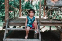 LAOS, LUANG PRABANG: Child sitting at hut and looking at camera — Stock Photo