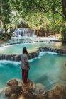 Vista laterale del turista barbuto in piedi a cascata con acqua blu . — Foto stock