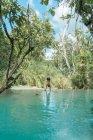 Человек, стоящий на руках у тропического озера — стоковое фото
