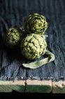 Nature morte d'artichauts crus sur table rustique — Photo de stock