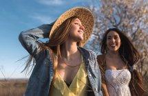 Веселий молодих gilrs, тримаючись за руки і прогулянки на природі в сонячний день — стокове фото