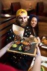 Uomo barbuto seduto nella caffetteria con la ragazza e prendere cibo da cameriere. — Foto stock